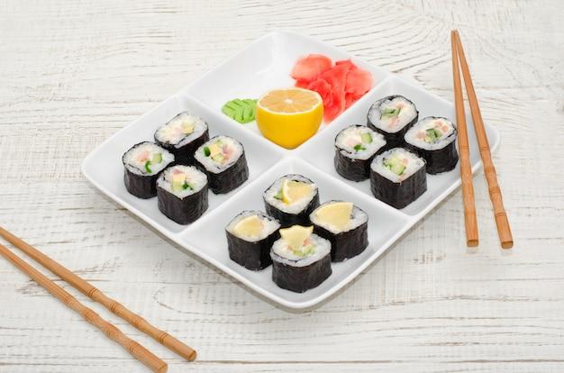 Piatto quadrato con una serie di rotoli sul tavolo di legno. bacchette, zenzero, limone. vista laterale