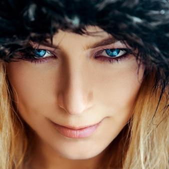 Ritratto quadrato di giovane donna carina con capelli biondi e occhi azzurri in cappello di pelliccia.