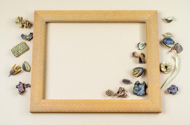 Cornice quadrata in legno con fiori secchi di vaniglia rotondi sullo sfondo pastello di carta