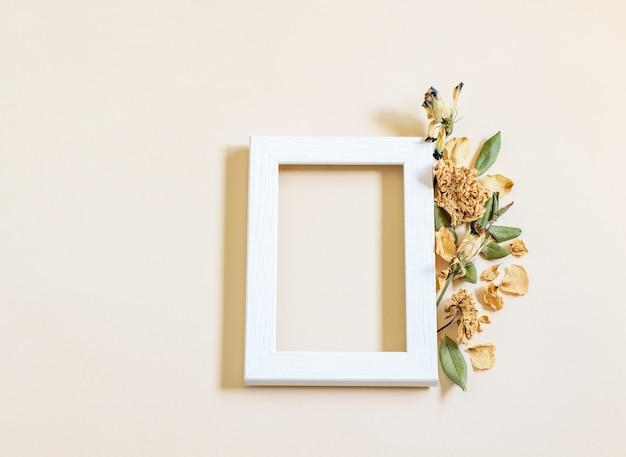 Cornice quadrata in legno, fiori secchi di lisiantum sullo sfondo della carta delicata beige.
