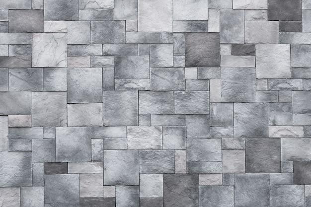 Fondo dei quadrati, struttura della parete di pietra, pavimento della roccia grigia. granito monocromatico, superficie in mattoni.