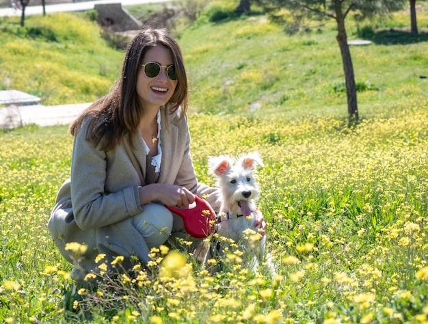 Accovacciata giovane donna guarda la telecamera con il suo cane schnauzer