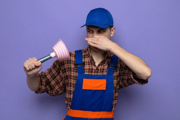 Schizzinoso naso chiuso giovane ragazzo delle pulizie che indossa l'uniforme e il cappuccio che tiene e guarda lo stantuffo