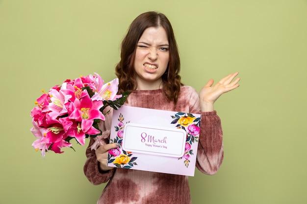 Schizzinosa mano allargata bella ragazza in felice festa della donna che tiene bouquet con biglietto di auguri