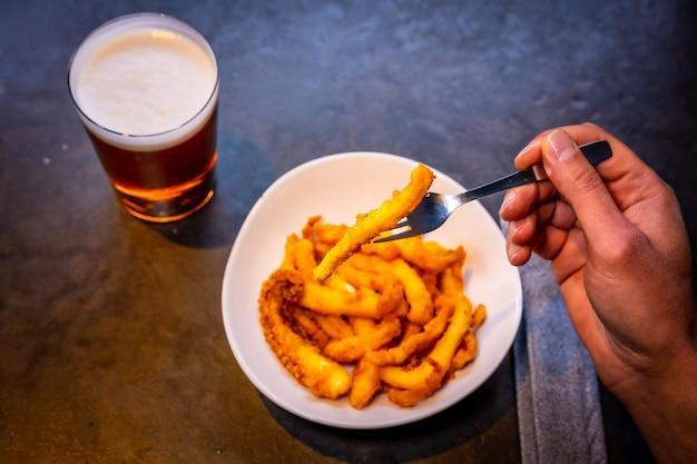 Calamaro impanato al limone accompagnato da una birra su fondo nero, su piatto bianco