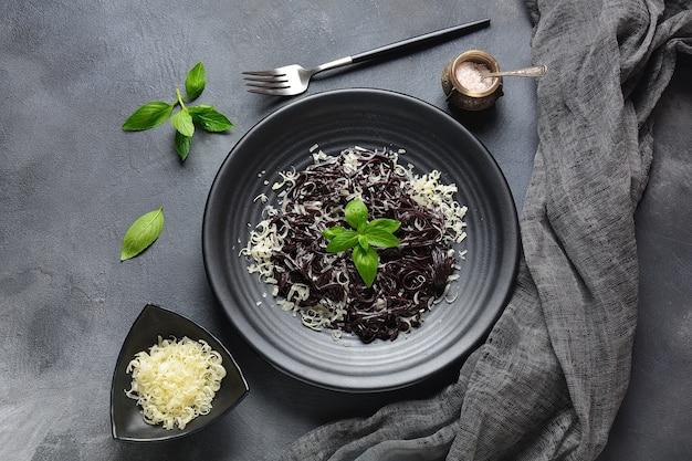 Pasta al nero di seppia con, parmigiano, foglie di basilico. spaghetti neri