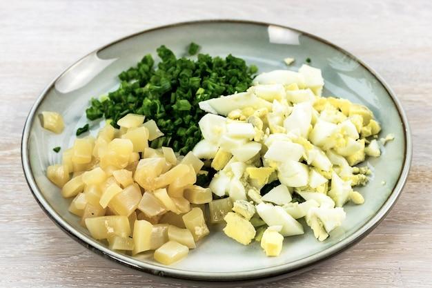 Insalata di calamari con uovo, cipolla verde ricetta passo-passo passo 5 mescolando gli ingredienti sul piatto blu grigio sul tavolo di legno bianco. avvicinamento. messa a fuoco selettiva. copia spazio