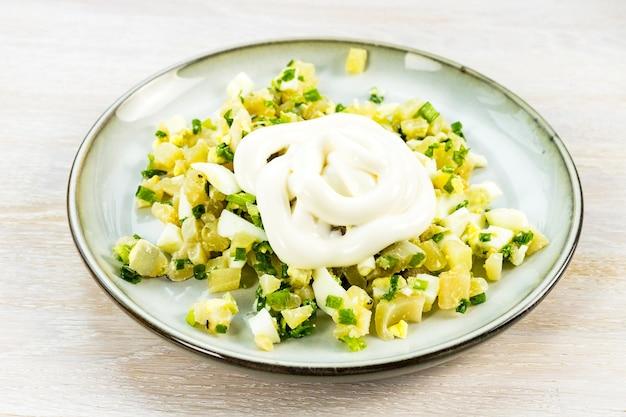 Insalata di calamari con uovo, cipolla verde ricetta passo-passo passo 6 condimento di maionese sul piatto blu grigio sul tavolo di legno bianco. avvicinamento. messa a fuoco selettiva. copia spazio