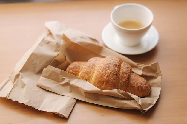 Sroissant e tazza di caffè sulla tavola di legno. mattina a casa.