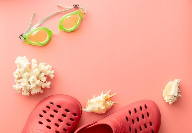 Sfondo estivo di coccodrilli, occhialini da nuoto, conchiglie, corallo su sfondo rosa