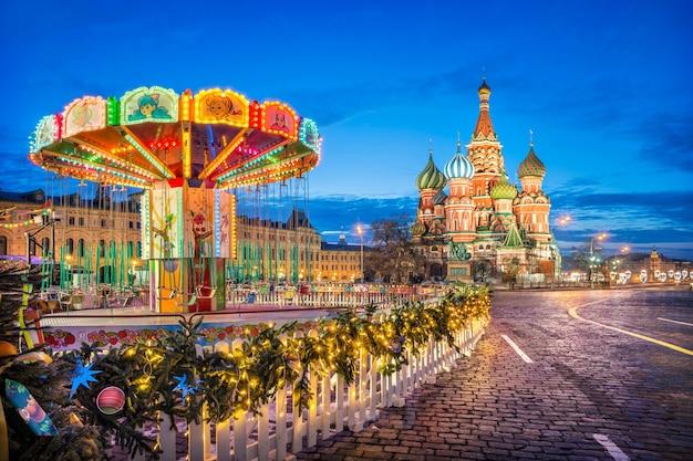 Cattedrale di san basilio sotto un cielo blu sulla piazza rossa di mosca e giostra per bambini alla luce delle lanterne in una mattina d'inverno