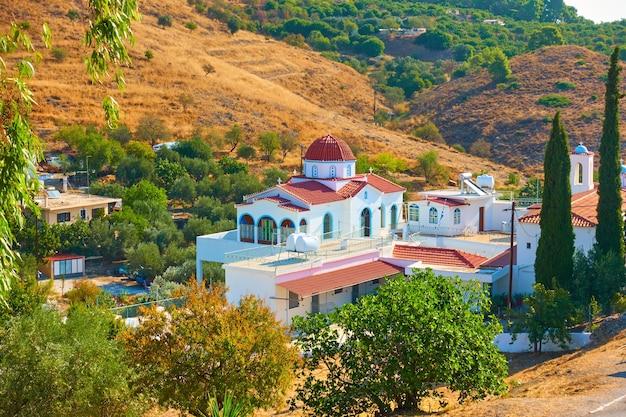 Monastero di santa caterina circondato da colline e giardini nell'isola di egina, grecia - paesaggio greco