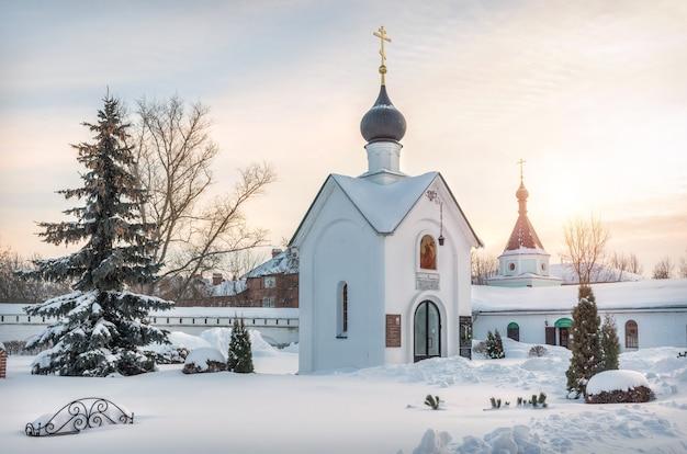 Cappella di san giorgio in inverno con pini e bellissima alba