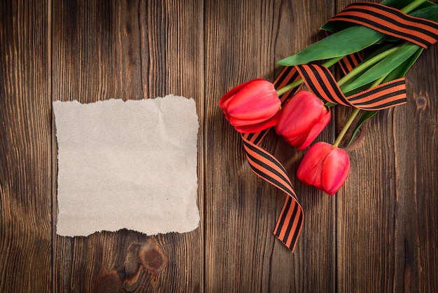 Nastro di san giorgio, tulipani rossi e biglietto di auguri di carta su fondo in legno. giorno della vittoria o giorno del difensore della patria.