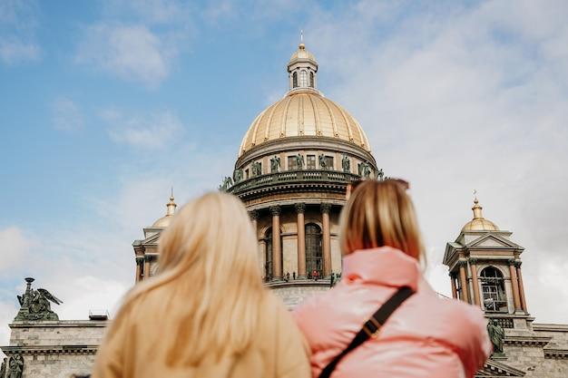 Cattedrale di sant'isacco a san pietroburgo. primo piano sfocato - due ragazze turistiche. focus sulla cattedrale. concetto di visite ed escursioni