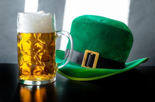 Cappello di giorno di san patrizio di un leprechaun e bicchiere di birra sul grigio