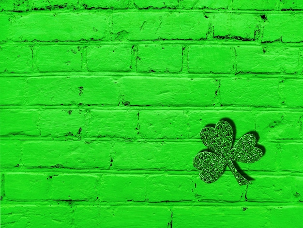 Il giorno di san patrizio vecchio muro di mattoni verdi con texture grunge e foglia di trifoglio. modello astratto. sfondo luminoso.