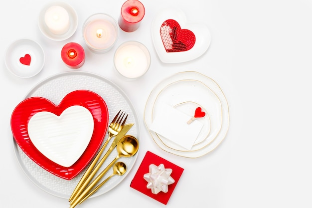 Regolazione della tavola di san valentino. piatti bianchi e rossi a forma di cuore, candele e posate sfondo bianco. concetto romantico
