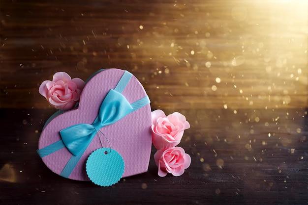 Il cuore e la rosa di rosa di san valentino della scatola di san valentino su fondo di legno scuro, copiano lo spazio