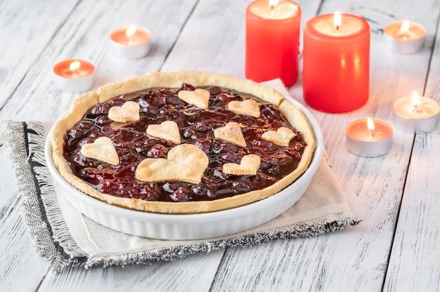 Crostata di marmellata di ciliegie di san valentino con candele accese