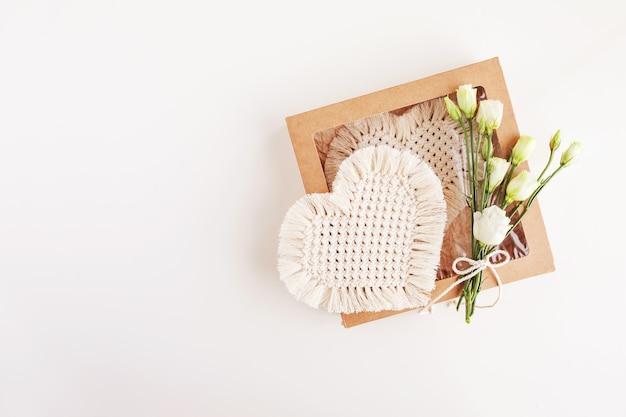 Confezione regalo di san valentino con decorazioni in macramè. materiali naturali, filo di cotone. macrame eco decorazioni, ornamenti, decorazioni fatte a mano. cuore.