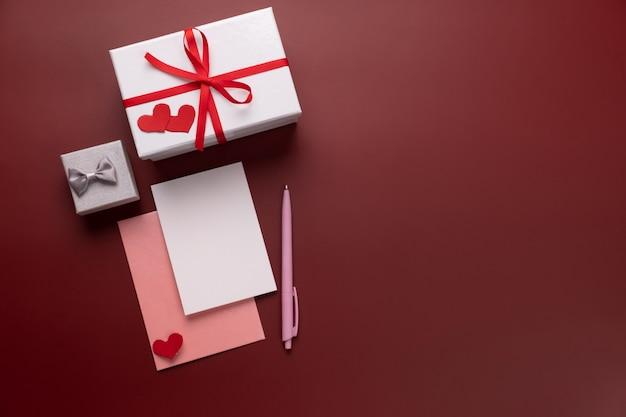 Lettera e regali di san valentino in scatole. copi lo spazio per il messaggio di amore. carta bianca con busta di carta rossa, mock up. vista piana, vista dall'alto