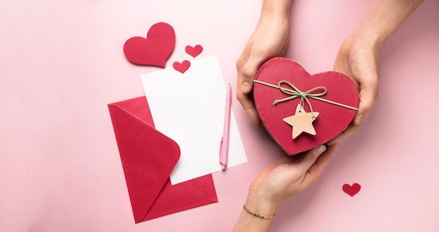 Lettera e regali di san valentino in scatola a forma di cuore nelle mani. copi lo spazio per il messaggio di amore. carta bianca con busta di carta rossa, mock up. vista piana, vista dall'alto