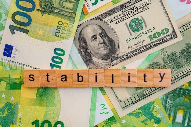 Iscrizione di stabilità su cubi di legno sulla trama di dollari americani e banconote in euro