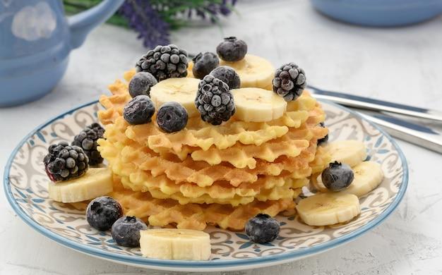 Pila di cialde belghe al forno su un piatto rotondo con frutti di bosco su un tavolo bianco, deliziosa colazione, primi piani