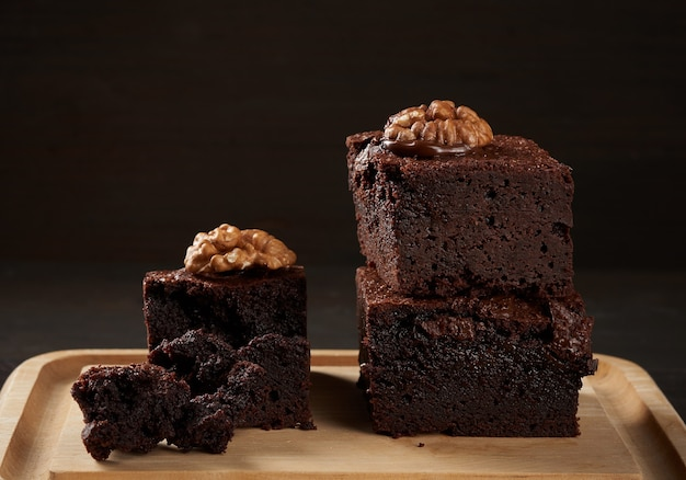 Pila di pezzi al forno di torta al cioccolato brownie con noci su una tavola di legno