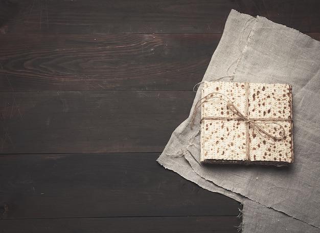 Pila di matzoh quadrato al forno su fondo di legno marrone