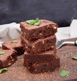 Pila di pezzi quadrati al forno di torta brownie al cioccolato con noci