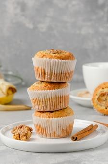 Pila di muffin alla banana con farina d'avena, noci e cannella su un piatto bianco su sfondo grigio cemento. dessert sano. copia spazio.
