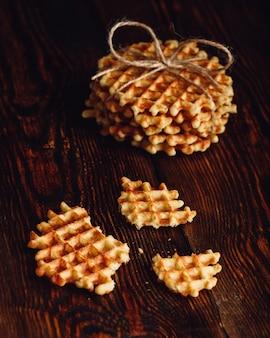 Pila di cialde belghe e pezzi di cialda sulla superficie in legno