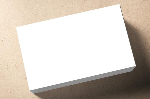 Pila di biglietti da visita in bianco su sfondo marrone