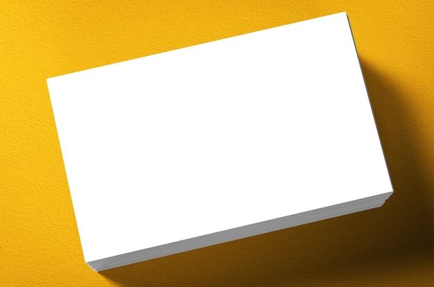Pila di biglietti da visita in bianco su sfondo giallo