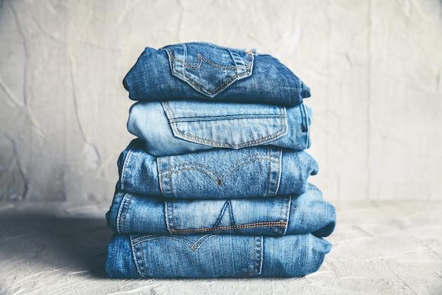 Pila di blue jeans su uno sfondo grigio