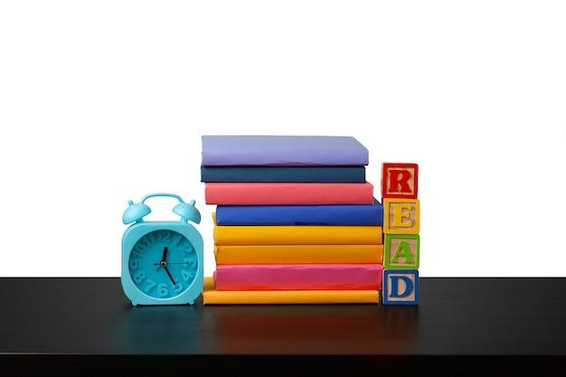 Pila di libri e sveglia tempo per leggere il concetto