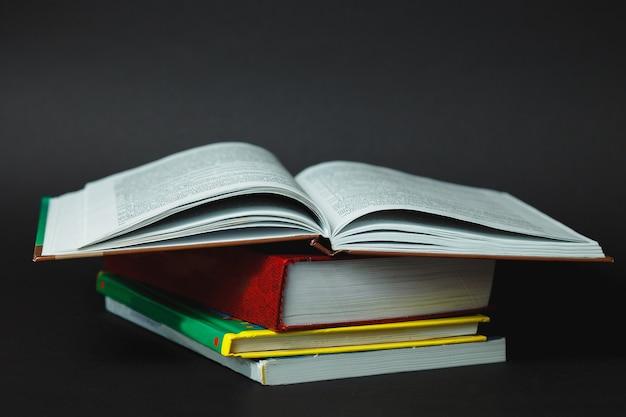 Pila di libri su sfondo nero. pila di libri