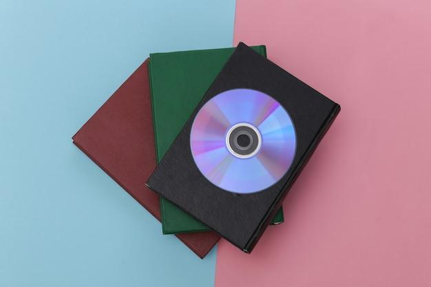 Pila di libri e cd su sfondo pastello blu-rosa. libri audio digitali
