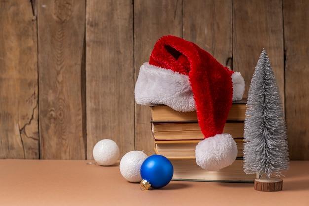 Pila di libri, decorazioni natalizie e cappello di babbo natale su fondo di legno.