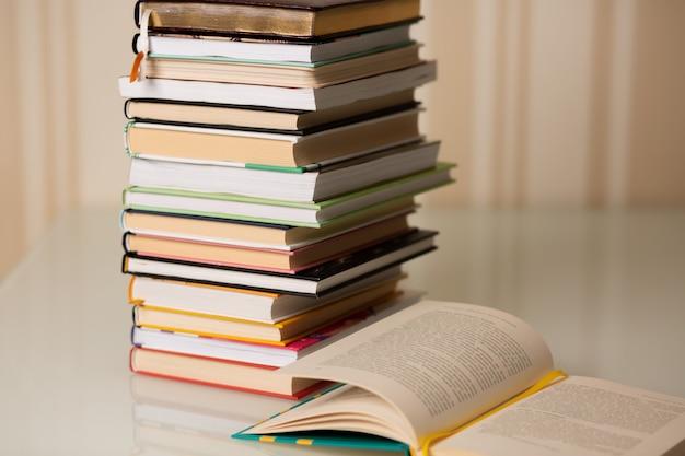 Pila di libri su una scrivania a casa. sfondo a righe beige. spazio vuoto