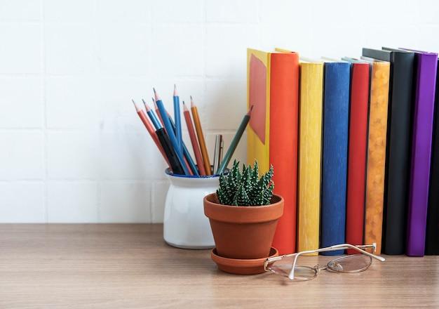 Pila di libri sul desktop. vari libri e forniture per ufficio sul tavolo
