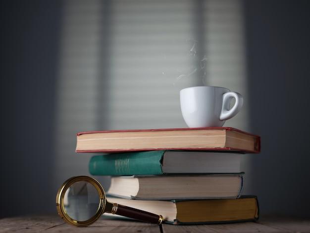Pila di libri, tazza di caffè espresso e lente d'ingrandimento