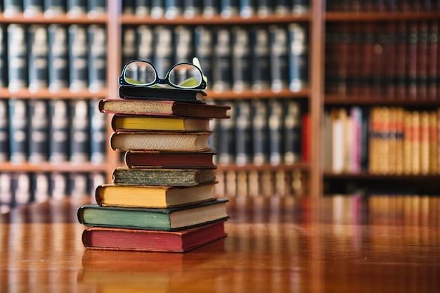 Pila di libri e bicchieri in biblioteca Foto Premium