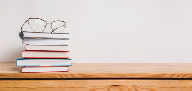 Una pila di libri e bicchieri sulla tavola di legno