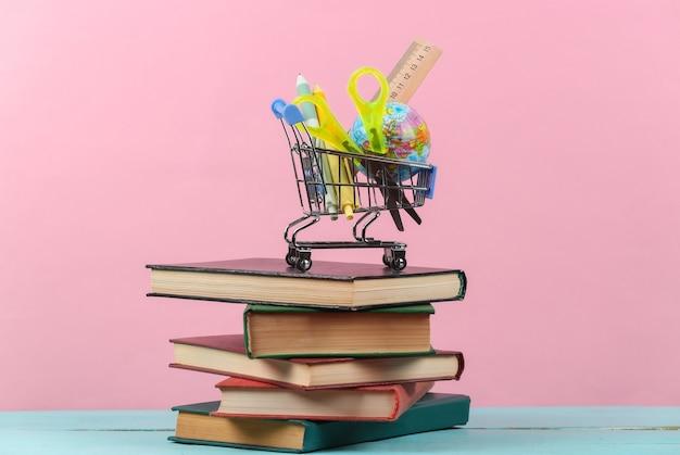 Pila di libri, carrello della spesa con materiale scolastico su sfondo rosa.