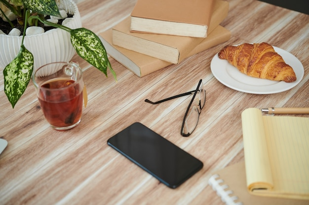 Pila di libri, smartphone, tè e croissant sul tavolo di uno studente universitario
