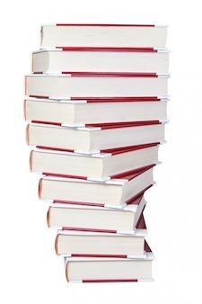 Una pila di primo piano a spirale dei libri su una parete bianca.
