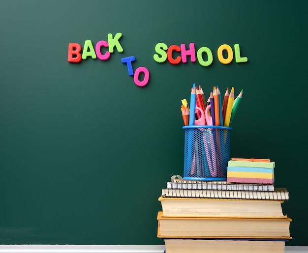 Pila di libri e articoli di cancelleria su sfondo vuoto gesso lavagna verde, torna a scuola